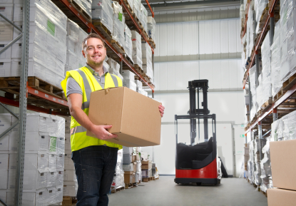 carrying cartons in a warehouse, wearing safety vest