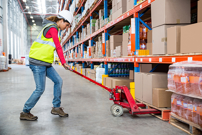 warehouse worker picking cartons from the floor level of a pallet rack