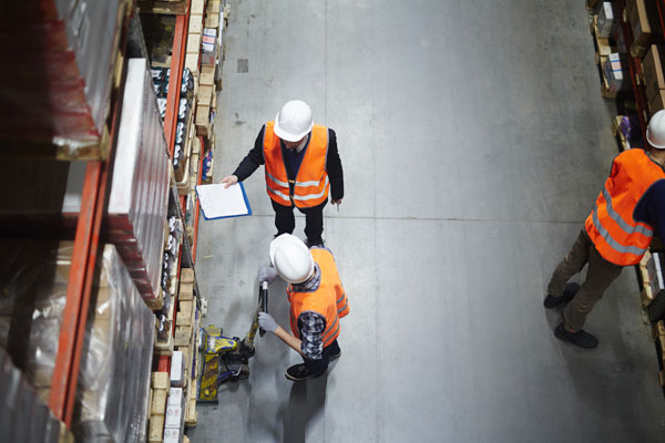 men working in a warehouse rack aisle