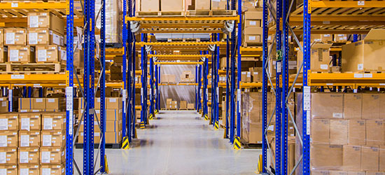 rack tunnel in a distribution warehouse, where forklifts pass through a cross-aisle.