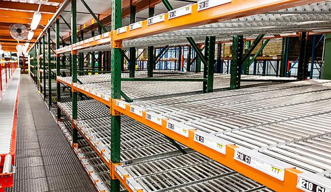 Carton flow tracks set into pallet rack in a distribution center