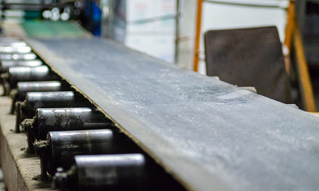 belt over roller conveyor in a gritty manufacturing facility