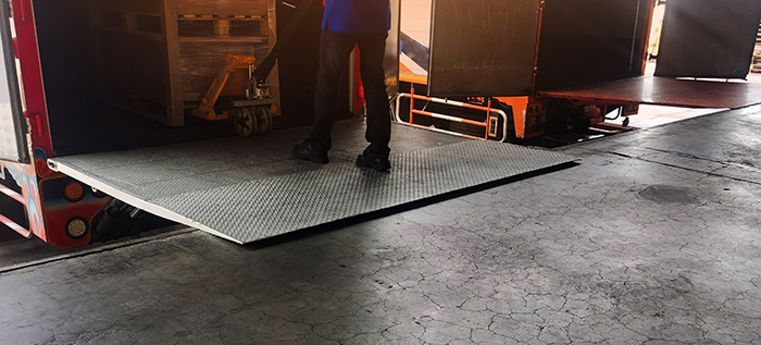 dock plate with a hand truck unloading at a warehouse shipping area.