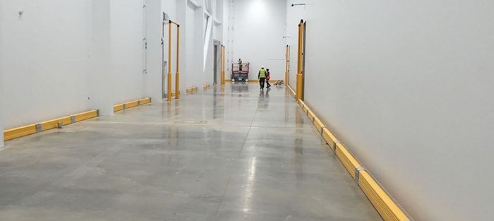 Hallway with guardrail lining the walls for safer operations.