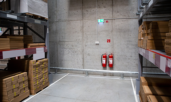 Pallet rack aisle in a warehouse, near fire extinguishers.
