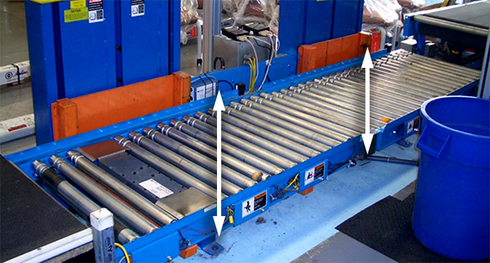 In-line lift along a conveyor line lowers and raises loads in mid-transport.