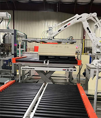 scissor lift at the end of conveyor line, integrated with robotic palletizer.