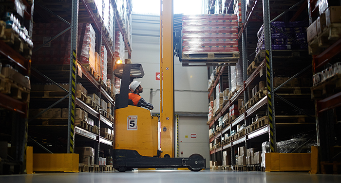 Warehouse rack with worker placing a pallet into tight space on a pallet rack