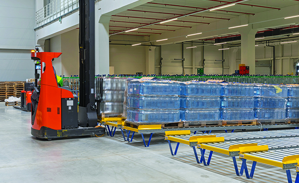 forklift loading gravity pallet conveyors in a warehouse.