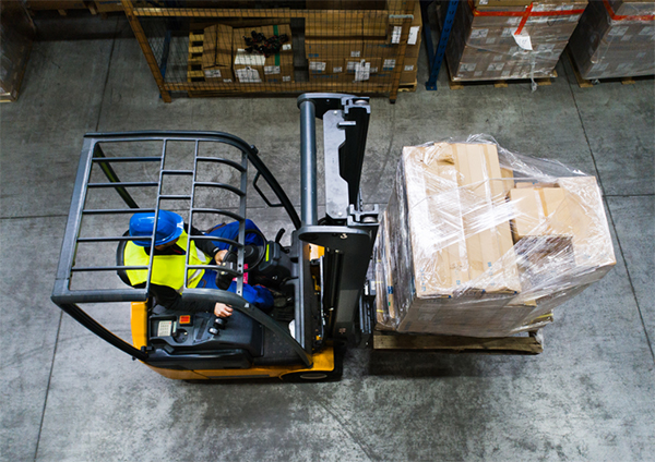 Forklift driver as seen from overhead in a warehouse. Forklift is in motion.