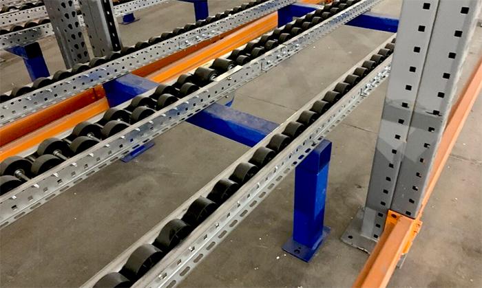 Magnum rollers mounted inside a pallet flow rack frame.