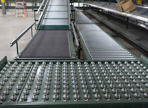 Ball transfer table mounted at a conveyor switchback in a large distribution center.