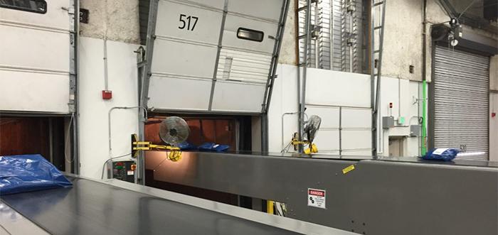 Extendable conveyors enter truck trailers